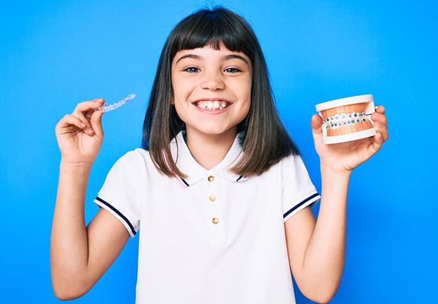 Giovane bambina sorridente tiene in mano un apparecchio ortodontico tradizionale e un apparecchio ortodontico
